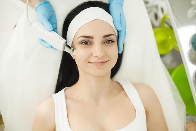 Mulher bonita e saudável tendo sua pele analisada por cosmetologista, usando analisador de pele