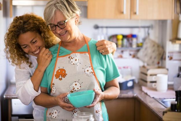 Mulher bonita e sênior madura na cozinha olhando para a mesa e cozinhando - anos 60 com óculos com sua filha, mostrando como cozinhar algo