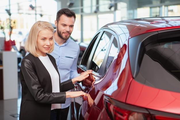 Mulher bonita e seu marido escolhendo novo automóvel para comprar