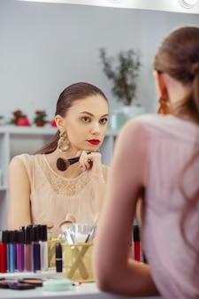 Mulher bonita e simpática olhando no espelho enquanto pensa em sua aparência