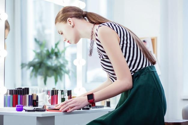 Mulher bonita e simpática olhando seus cosméticos enquanto quer se maquiar