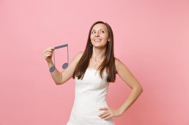 Mulher bonita e sonhadora em vestido branco segurando nota musical, escolhendo staff, músicos ou dj