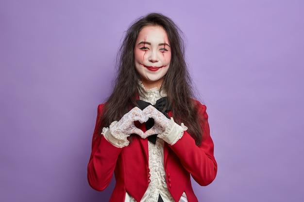 Mulher bonita e sorridente com rosto de fantasma pálido de maquiagem medrosa e cicatrizes de sangue faz um gesto de coração e expressa o amor por estar na festa de halloween isolado sobre a parede roxa