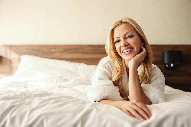 Mulher bonita e sorridente de meia-idade com longos cabelos loiros e rosto fresco deitada em uma cama limpa em um quarto de hotel com um roupão branco