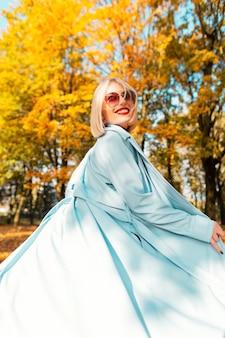 Mulher bonita e sorridente feliz com lábios vermelhos em um casaco azul elegante com óculos de sol, caminhando no parque com folhagem de outono amarela brilhante