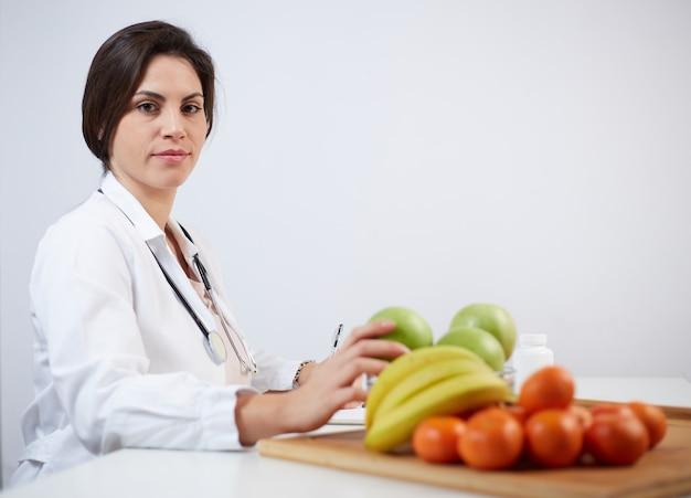 Mulher bonita e sorridente nutricionista com frutas saudáveis