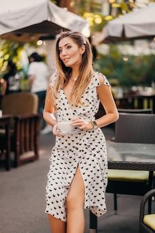 Mulher bonita e sorridente, usando um elegante vestido branco estampado, sentada em um café de rua com uma xícara de cappuccino