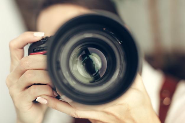 Mulher bonita é um fotógrafo profissional com câmera dslr