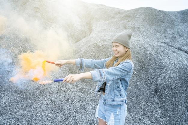 Mulher bonita ela está jogando uma cor de fumaça de fogos de artifício no lugar do rock grand canyon