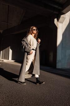 Mulher bonita elegante com cabelo encaracolado em um casaco longo vintage, blusa, calças e botas com óculos de sol entra na cidade perto da arquitetura de concreto à luz do sol e à sombra.