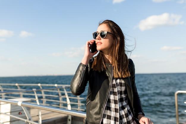 Mulher bonita elegante com cabelo escuro, jaqueta de couro e óculos escuros falando ao telefone perto do mar