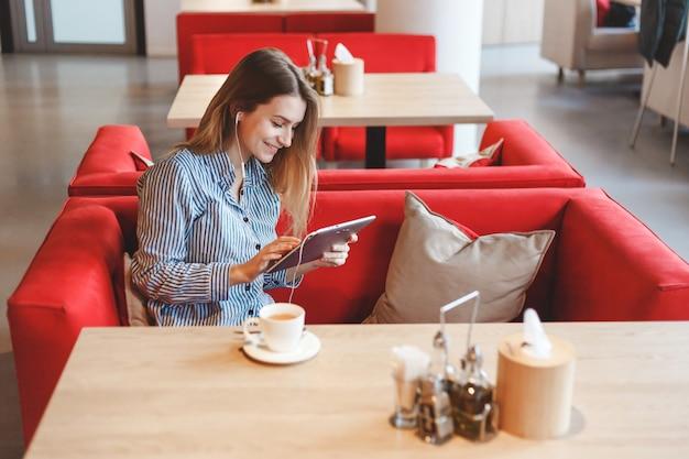 Mulher bonita elegante com computador tablet bebendo chá no café