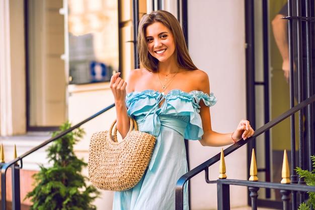 Mulher bonita elegante com vestido da moda e bolsa de palha