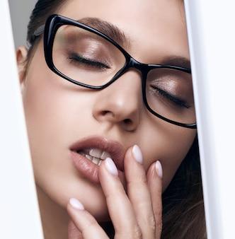 Mulher bonita elegante em um óculos preto da moda
