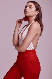 Mulher bonita elegante em um terno vermelho elegante com rosa