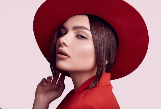 Mulher bonita elegante em um terno vermelho elegante e chapéu largo