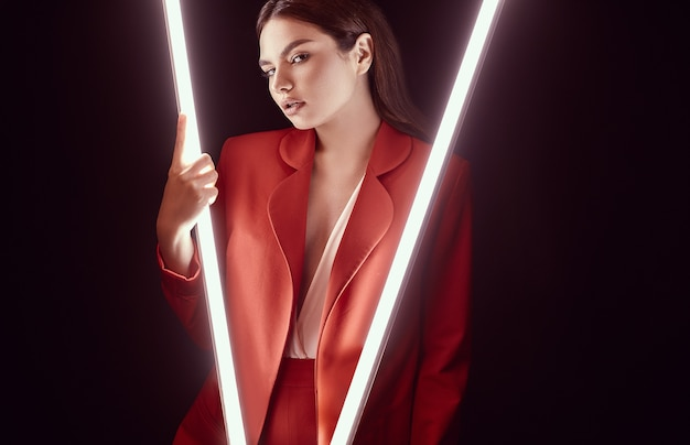 Mulher bonita elegante em um terno vermelho elegante posando com luzes de neon