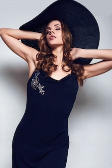 Mulher bonita elegante em um vestido preto e chapéu