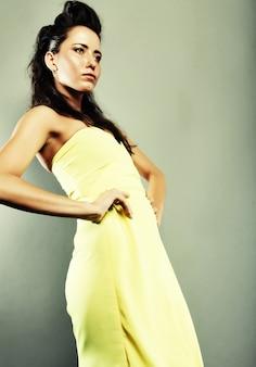 Mulher bonita elegante em vestido amarelo