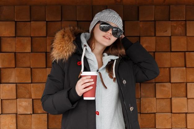 Mulher bonita elegante jovem hippie com um chapéu de malha em óculos de sol em uma jaqueta preta de inverno com um capuz de pele em um moletom elegante com um copo de bebida quente se passando perto de uma parede de madeira ao ar livre. menina moderna
