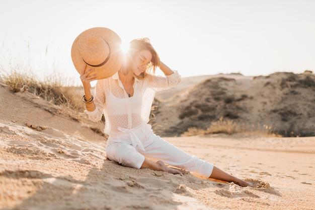 Mulher bonita elegante na areia do deserto com roupa branca e chapéu de palha no pôr do sol