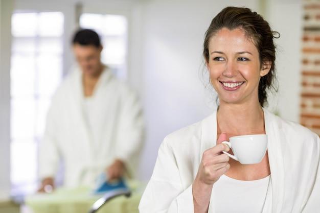 Mulher bonita, em, bathrobe, tendo, um, xícara chá, em, cozinha, e, homem, passar roupa, atrás de, dela