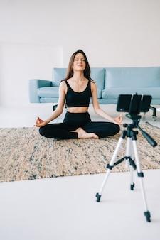 Mulher bonita em boa forma meditando na frente da câmera no tripé, fazendo ioga em casa