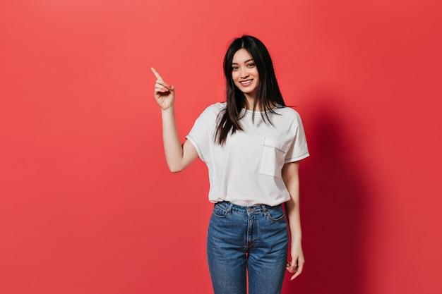 Mulher bonita em calças jeans mostra o dedo para colocar o texto na parede vermelha