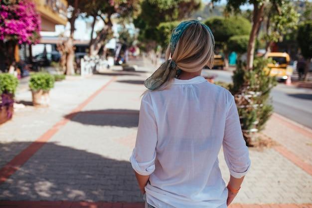 Mulher bonita em camisa branca andando pelas ruas da turquia