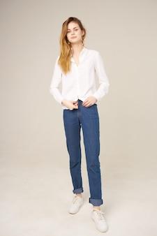 Mulher bonita em camisa branca e jeans com cabelo vermelho comprido