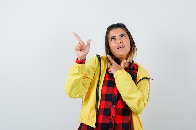 Mulher bonita em camisa, jaqueta apontando para o canto superior esquerdo, olhando para cima e olhando pensativa, vista frontal.