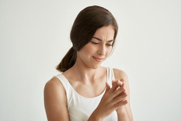Mulher bonita em camiseta branca problemas de saúde dor no braço ferido