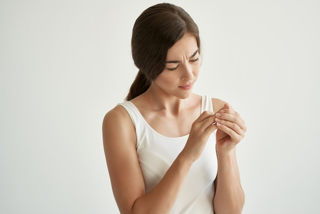 Mulher bonita em camiseta branca problemas de saúde feridos dor no braço