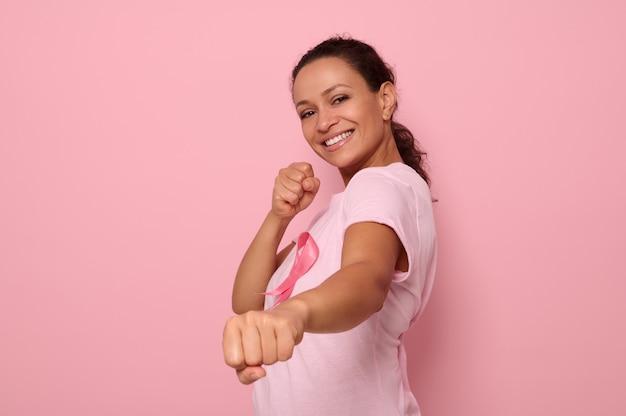 Mulher bonita em camiseta rosa e fita de conscientização do câncer em posição de combate para marcar a luta contra o câncer, em homenagem a 1 de outubro, sorri olhando para a câmera, fundo colorido, espaço de cópia