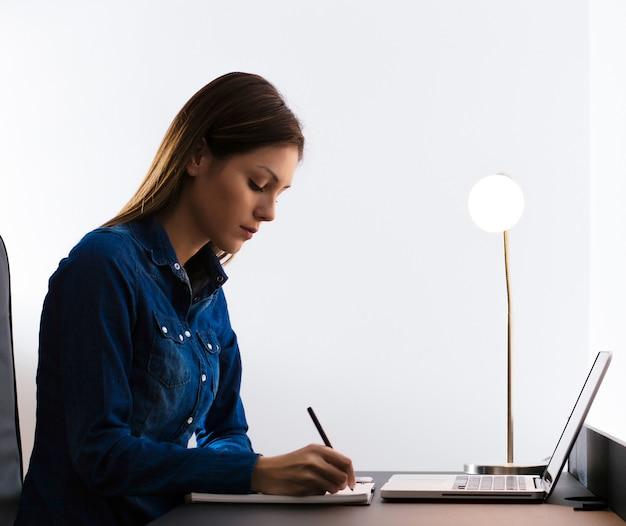 Mulher bonita em casa escrevendo e trabalhando com o diário e o computador portátil