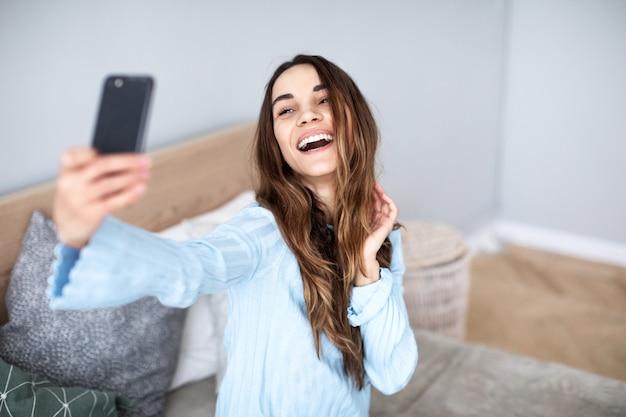 Mulher bonita em casa fazer selfie no celular. estilo de vida.