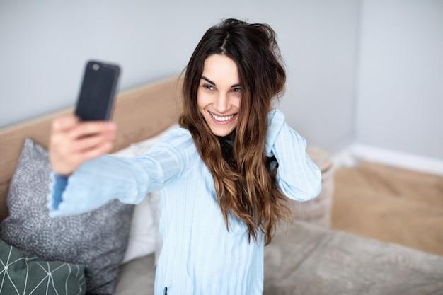 Mulher bonita em casa no sofá fazer selfie no celular. estilo de vida.