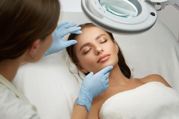Mulher bonita em clínica de cosmetologia deitada com os olhos fechados e fazendo teste profissional de tratamento facial pelo cosmetologista