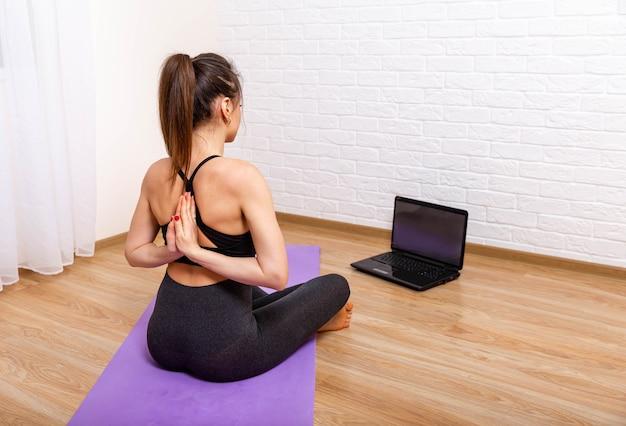 Mulher bonita em colchonete treinando online com laptop