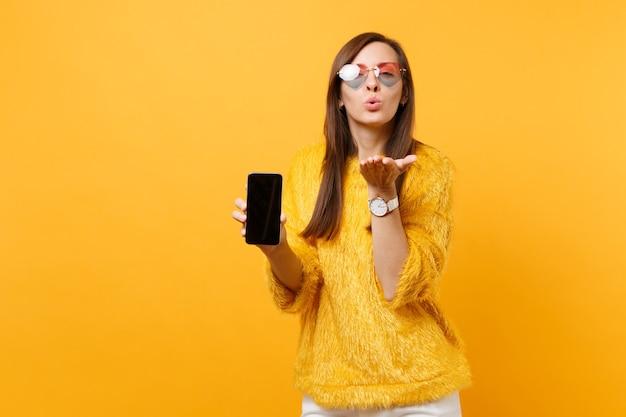 Mulher bonita em copos de coração soprando lábios enviando ar beijo, segure o telefone móvel com tela vazia preta em branco isolada no fundo amarelo brilhante. pessoas sinceras emoções, estilo de vida. área de publicidade.
