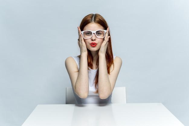 Mulher bonita em copos se senta em uma mesa, espaço leve, posando de emoções