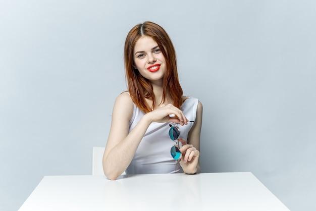 Mulher bonita em copos se senta em uma mesa