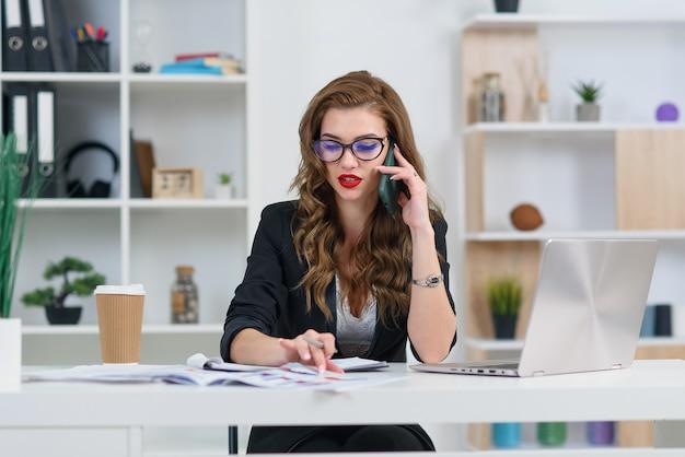 Mulher bonita em copos tendo conversa telefônica de negócios