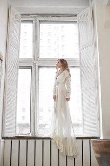 Mulher bonita em cueca branca e lingerie em casa no banheiro. uma mulher apaixonada está descansando