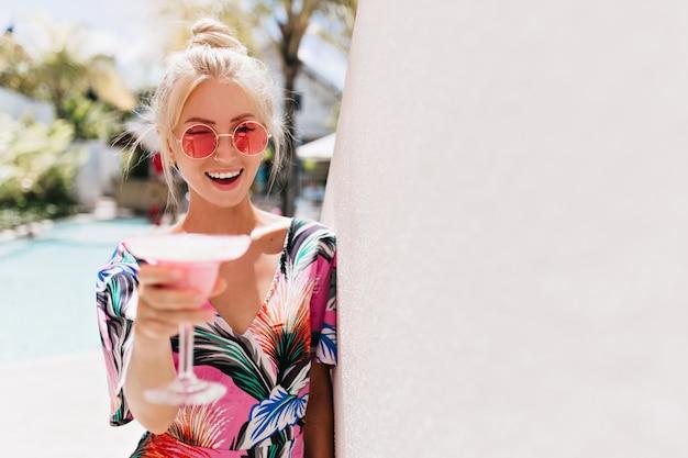 Mulher bonita em elegantes óculos cor de rosa, degustação de bebidas de frutas.