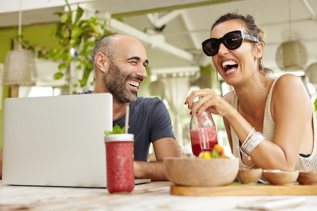 Mulher bonita em elegantes óculos de sol segurando um copo de suco fresco e rindo enquanto seu lindo amigo com barba contando-lhe uma história engraçada.