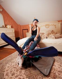 Mulher bonita em equipamento de mergulho, sentada na cama