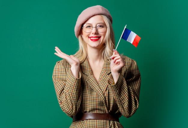 Mulher bonita em estilo casaco e chapéu com bandeira francesa na parede verde