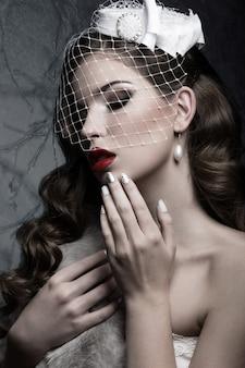 Mulher bonita em estilo gótico com maquiagem de noite e unhas vermelhas com espinhos. foto tirada em um estúdio em um fundo vermelho.