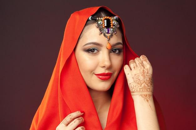 Mulher bonita em estilo oriental com mehendi em fundo escuro